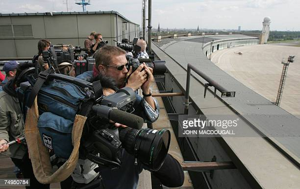 Cameramen shoot footage from the roof of Tempelhof airport's main terminal in Berlin 29 June 2007. Tempelhof airport is expected to cease all flight...