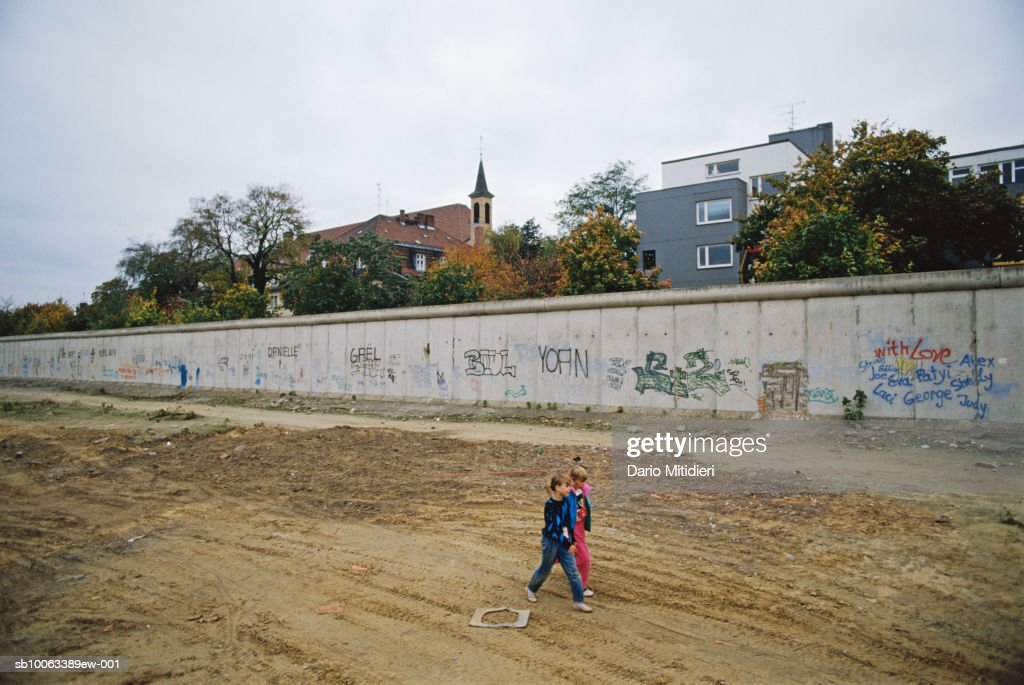 Berlin, Germany, children (6-7) walking down Bernauer Strasse with preserved part of Berlin Wall : News Photo