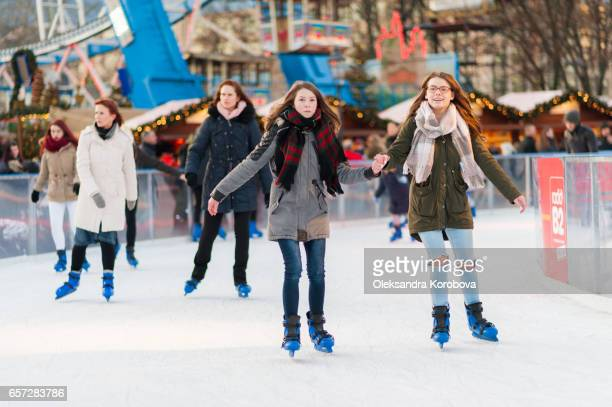 berlin, germany. december 21, 2016. friends skating on the frozen surface of the an ice rink during a winter fair. - istock stock-fotos und bilder