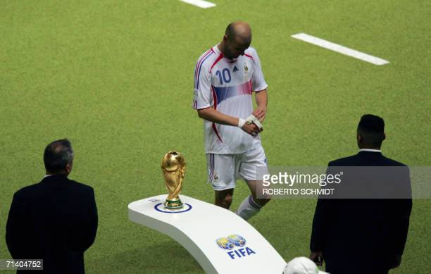 French midfielder Zinedine Zidane walks past the World Cup trophy being guarded by security as he leaves the pitch after getting a red card for...