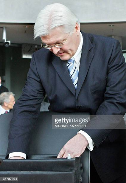 German Foreign Minister FrankWalter Steinmeier takes something out of his briefcase before testifying before a parliamentary committee probing claims...