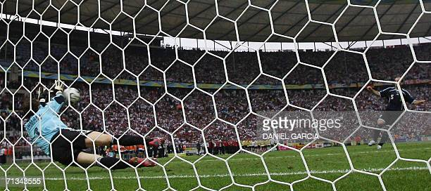 German goalkeeper Jens Lehmann dives to make the winning save against Argentinian midfielder Esteban Cambiasso during a penalty shootout at the end...