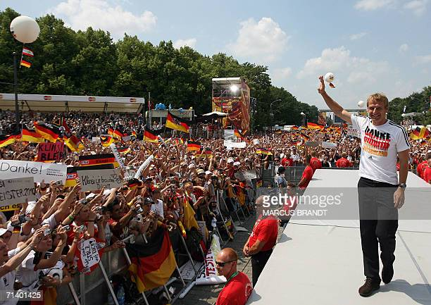 German head coach Juergen Klinsmann waves to supporters from the stage 09 July 2006 at the Fan Fest in Berlin One million people took over central...