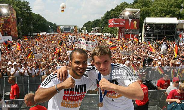 German midfielder David Odonkor and forward Lukas Podolski cheer on the stage 09 July 2006 at the Fan Fest in Berlin One million people took over...