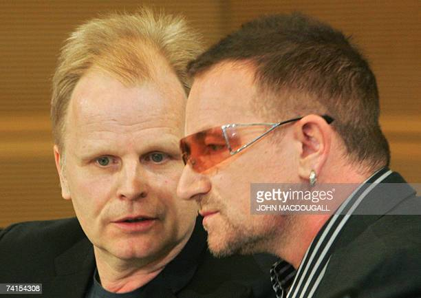 German pop star Herbert Groenemeyer confers with Irish pop band U2 frontman Bono as they address a press conference following the release of the DATA...