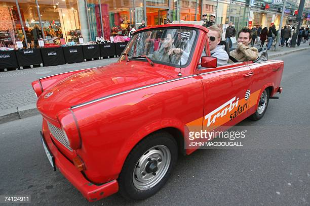 German youths enjoy a ride in a convertible Trabant through the streets of Berlin 24 April 2007 The Trabant was the former east Germany's 'People...