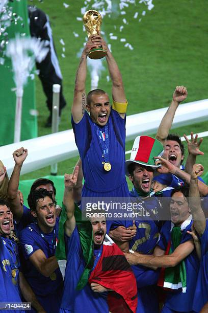 Italian defender Fabio Cannavaro hoists the World Cup trophy into the air as they celebrate the team's victory in the World Cup 2006 final football...