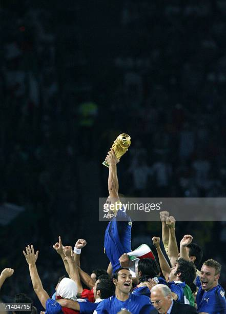 Italian defender Fabio Cannavaro holds up the World Cup trophy into the air as the team celebrates their victory in the World Cup 2006 final football...