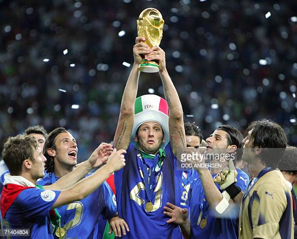 Italian defender Marco Materazzi holds up the 2006 World Cup trophy after Italy won their final football match against France at Berlins Olympic...