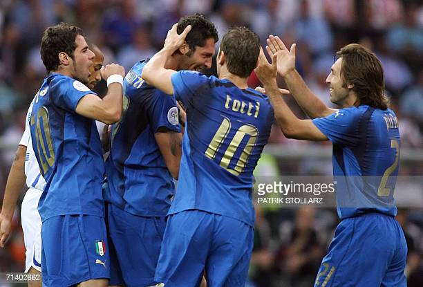 Italian defender Marco Materazzi is congratulated by his teammates Francesco Totti Simone Perrotta and Andrea Pirlo after scoring the first goal of...