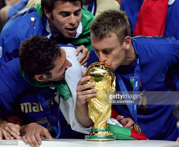 Italian defender Marco Materazzi looks on as Italian midfielder Daniele De Rossi kisses the World Cup trophy following their victory in the World Cup...