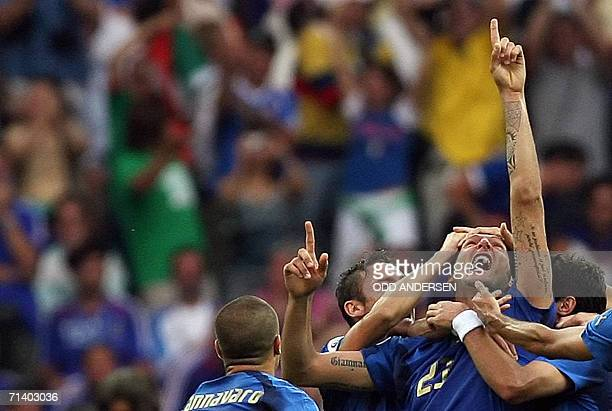 Italian defender Marco Materazzi points skyward as he celebrates scoring a goal with teammates during the World Cup 2006 final football match between...