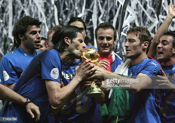 Italian midfielder Francesco Totti hold the World Cup trophy while Vincenzo Iaquinta kisses it after the World Cup 2006 final football game Italy...