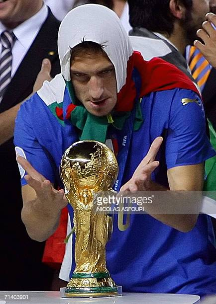 Italian midfielder Francesco Totti with his national flag on his head kisses the 2006 World Cup trophy after Italy won the final football match...