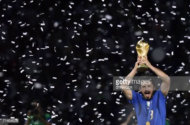 Italian midfielder Gennaro Gattuso holds up the 2006 World Cup trophy after Italy won their final football match against France at Berlin?s Olympic...