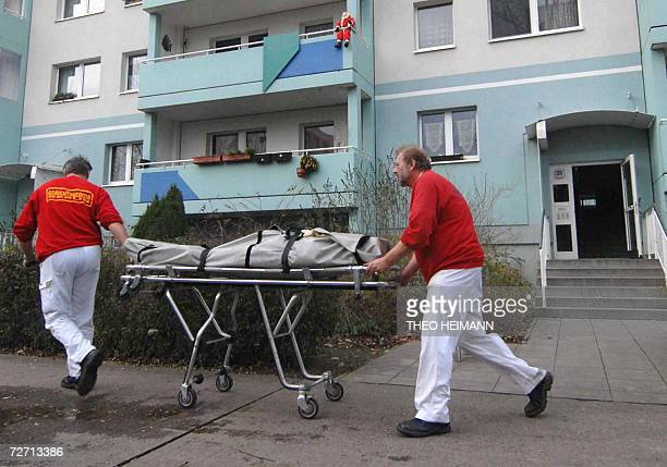 Paramedics stretcher a body from a building in Berlin's eastern Marzahn district 04 December 2006 The bodies of a 53yearold woman her two adult...
