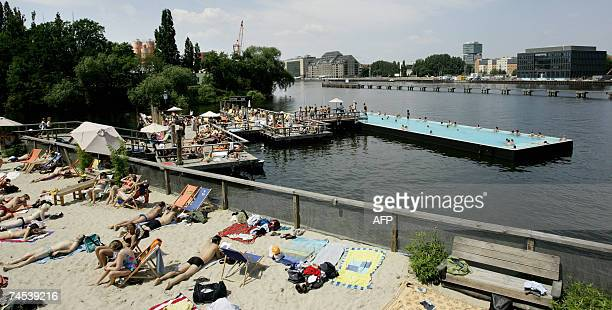 People enjoy a swim in a swimming pool as others relax on a beach set up on the river Spree in Berlin 11 June 2007 are unusually high in the German...