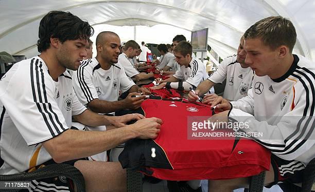 Players of the German national football team Michael Ballack David Odonkor Philipp Lahm Timo Hildebrand und Lukas Podolski sign autographs on jerseys...