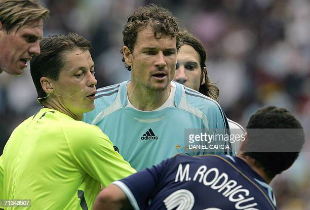 Referee Lubos Michel of Slovakia steps in as Argentinian midfielder Maxi Rodriguez and German goalkeeper Jens Lehmann exchange words during the...