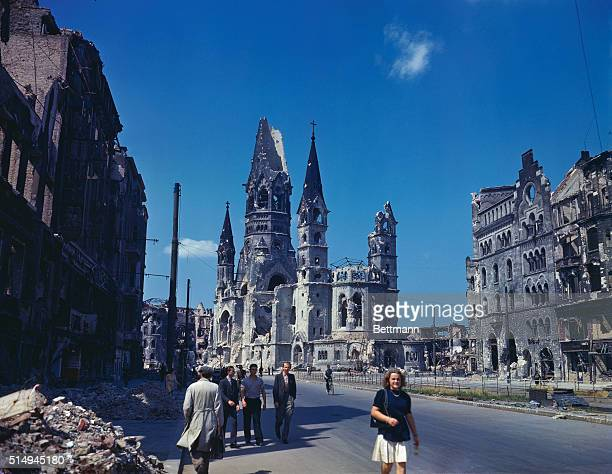 Ruins of Kaiser Wilhelm Memorial Church seen from down a street lines with bombed buildings Some pedestrians are also seen walking down the middle of...