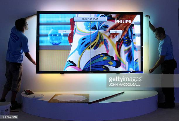 Technicians install a 100inch LCD TV with ambilight at Dutch electronics giant Philips' stand at Berlin's IFA Consumer Electronics trade fair 30...