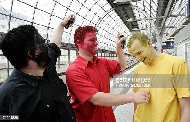 Three supporters of the German national football team paint their faces with black red and yellow the colours of the German flag 20 June 2006 at the...