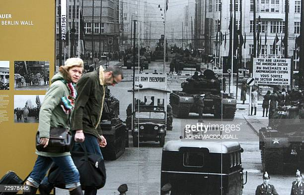 Two people walk past a giant photograph featuring US and Soviet Russian tanks during a stand off at Berlin's Checkpoint Charlie in October 1961 at an...