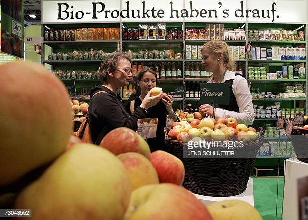Visitors try some apples 19 January 2007 at an organic food booth on the fairgrounds in Berlin where the 72nd 'Green Week' has opened to the public...