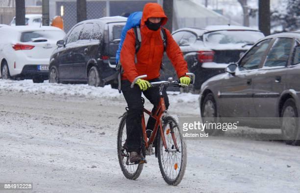 Berlin in einem geschlossenen Schneekleid Die Autos tragen ein weisses Kleid wie hier in der HeinrichHeineStrasse Radfahrer mit farbiger...