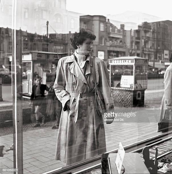 Berlin in the postwar period Street sceene of the Kurfürstendamm a woman looking at the window of a shop Photographer Ernst Hahn