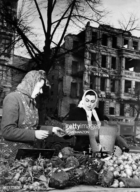 Berlin inhabitants buy rare and expensive vegetables at Berlin market in December 1948 during the Berlin blockade.
