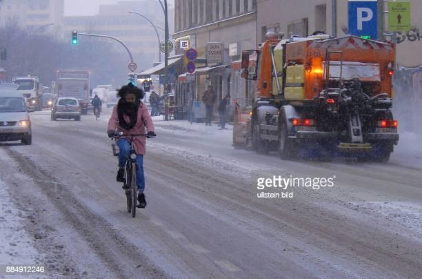 Berlin ist in einem geschlossenen Schneekleid Die Autos tragen ein weisses Kleid wie hier in der Brueckenstrasse Radfahrer mit farbiger...