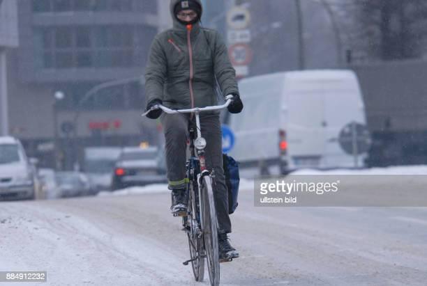 Berlin ist seit letzte Nacht in einem geschlossenen Schneekleid die Autos tragen ein weisses Kleid wie hier in der Brueckenstrasse Radfahrer fahren...