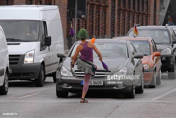 Berlin Kreuzberg Strassenkünstlerin jongliert an einer roten Ampel an der Oberbaumbruecke