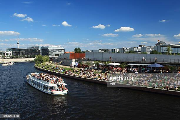 Berlin - many people sitting on the promenade near Spree river and enjoying the summer
