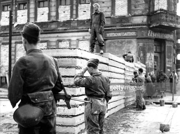Bernauer Strasse Baumassnahmen an der Mauer Ersatz der Mauersteine durch Betonplatten Grenzsoldaten der NVA bauen unter Bewachung die Betonplatten...