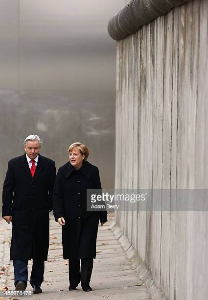 Berlin Mayor Klaus Wowereit and German Chancellor Angela Merkel walk along a section of the former Berlin Wall during celebrations for the 25th...