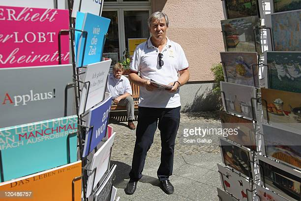 Berlin Mayor Klaus Wowereit walks out of a bookshop past postcards during a walking tour in Charlottenburg district on August 6 2011 in Berlin...
