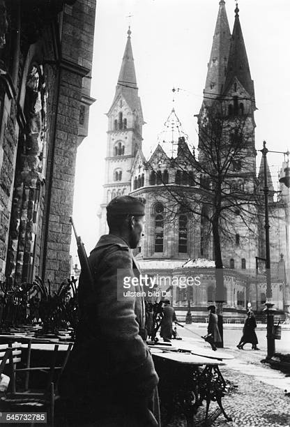Berlin memorial church after the air raid of 22/ in the foreground a soldier