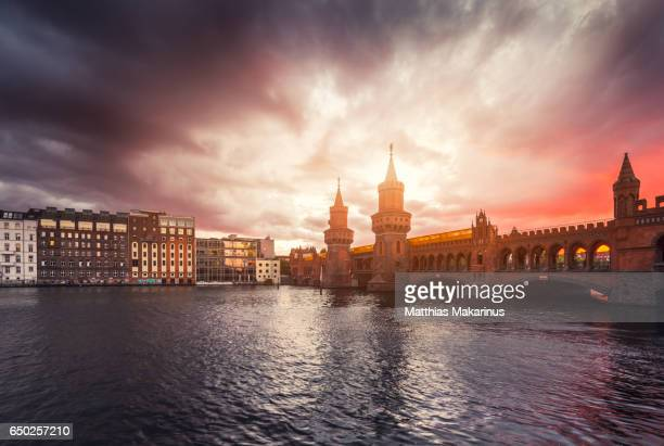 Berlin Oberbaum bridge with dramatic summer storm sunset sky with traffic