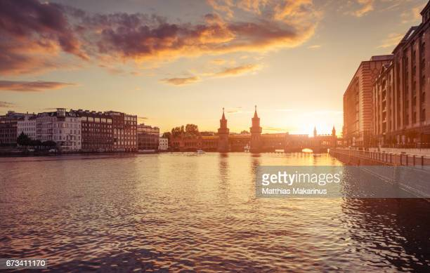 berlin oberbaum bridge with dramatic summer sunset sky - kreuzberg stock photos and pictures