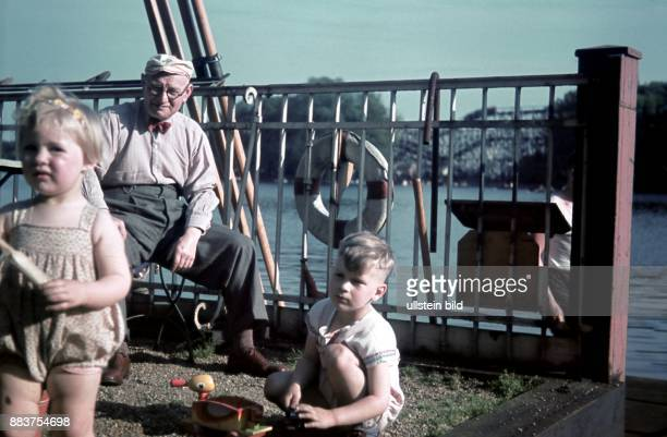 Berlin old man angling with two little children at the Spree river near Treptow Park