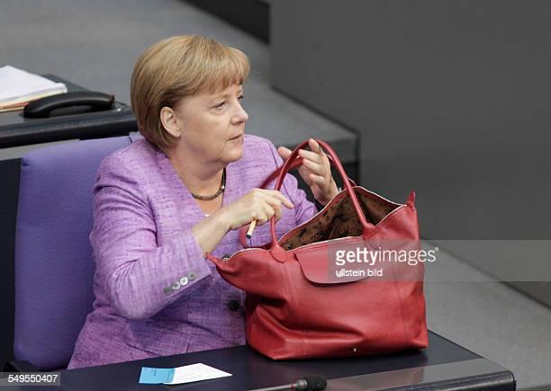 Berlin, Plenum Bundestag / Haushalt: Bundeskanzlerin Angela Merkel greift nach ihrer Handtasche