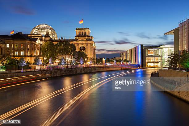 Berlin - Reichstag building/ german parliament building at blue hour with light trails of a boat