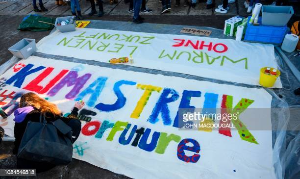 Berlin schoolchildren paint a giant banner reading Climate Strike in front of Germany's Bundestag lower house of parliament during a Friday strike...