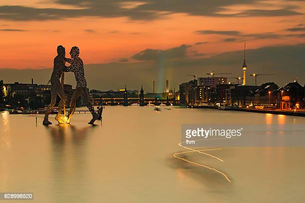 Berlin skyline with famous molecule men and TV-Tower in a colorful sunset