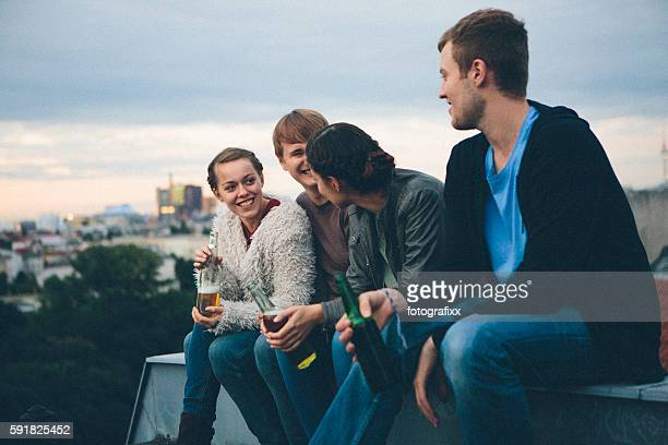 berlin: small group, young adults on rooftop, talking, drinking beer - blue hour stock-fotos und bilder