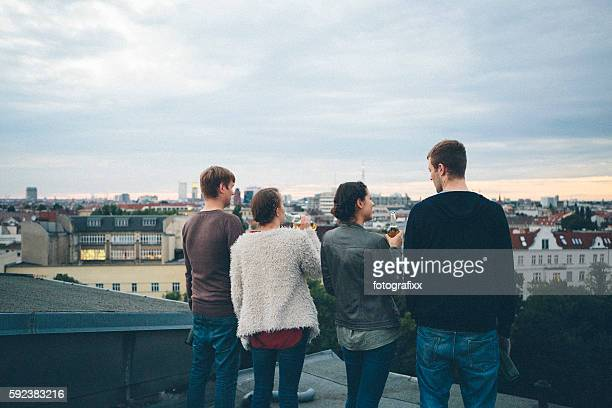 Berlin: small group, young adults on rooftop, talking, drinking beer