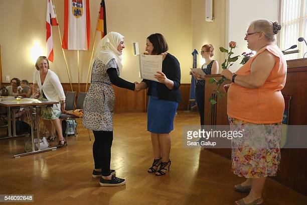 Berlin State Senator for Work Integration and Women Dilek Kolat awards Syrian refugee Marwad Khaled a certificate of completion for A1 beginner's...