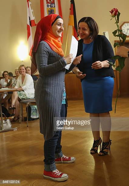 Berlin State Senator for Work Integration and Women Dilek Kolat awards Syrian refugee Zeinab Asselden a certificate of completion for A1 beginner's...